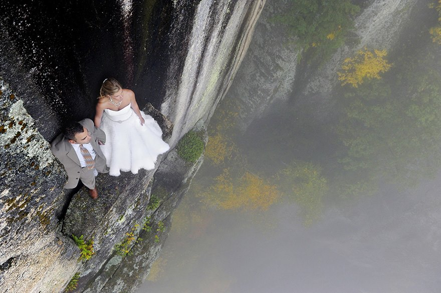 A couple peer over the ledge 350m above ground. Image: Philbrick Photography